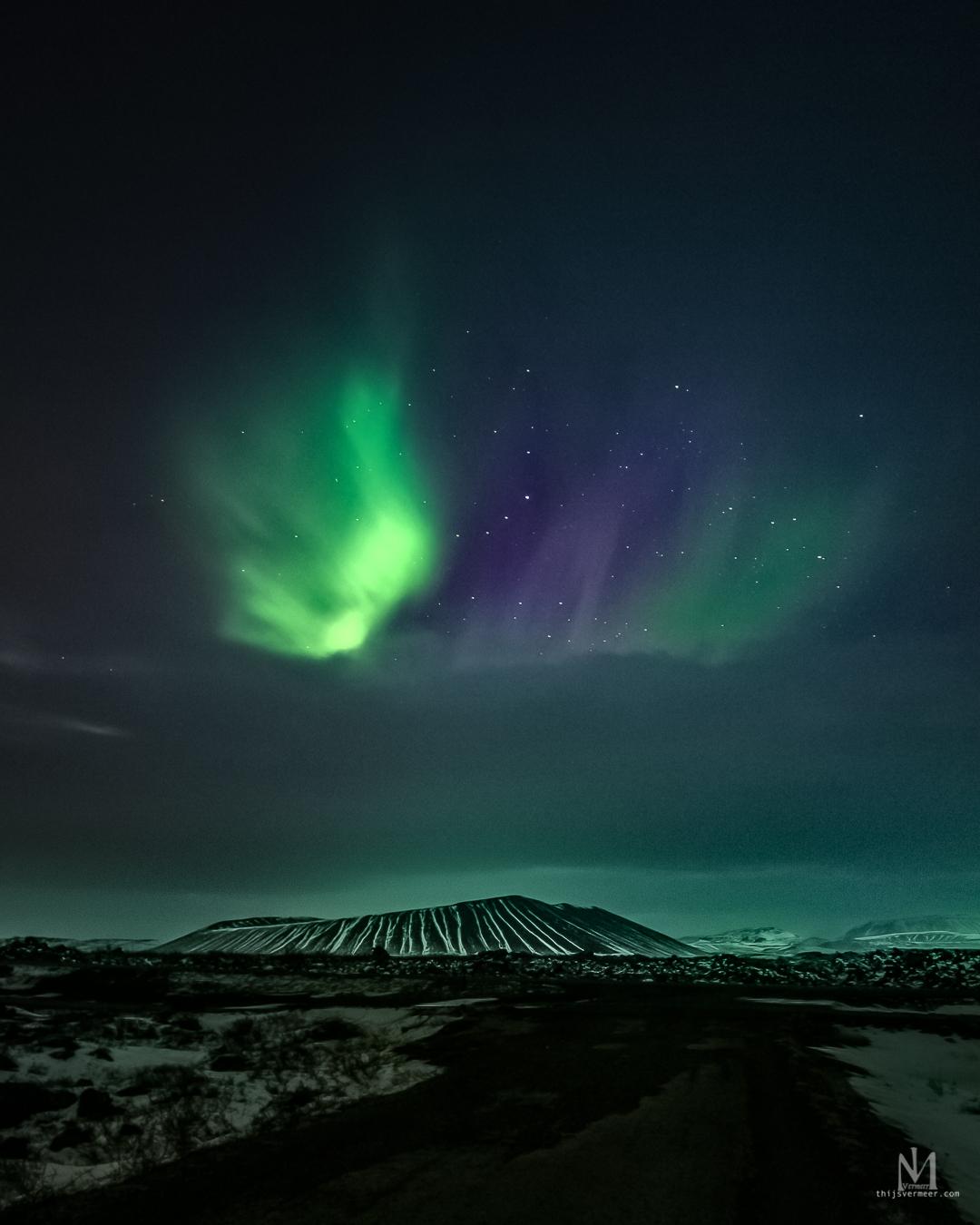 Noorderlicht boven Hverfjall vulkaan IJsland - Middernacht in een ijzige poolwind in noord IJsland maakte ik deze foto. Het was bewolkt maar ik zag door de wolken heen dat het noorderlicht erg act - foto door Thijsvermeer op 16-04-2021 - locatie: Dimmuborgir, IJsland - deze foto bevat: noorderlicht, nachtfotografie, astro, nacht, sterren, aurorborealis, vulkaan, ijsland, longexposure, lucht, atmosfeer, ecoregio, natuurlijke omgeving, natuurlijk landschap, aurora, atmosferisch fenomeen, horizon, landschap, astronomisch object