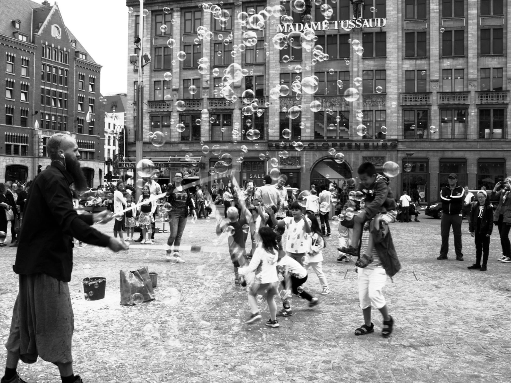 bellenblaas - gezellig op damplein in Amsterdam - foto door Gooiseroos op 13-07-2017 - deze foto bevat: man, vrouw, mensen, amsterdam, straat, markt, stad, kinderen, meisje, zwartwit, beweging, plein, feest, straatfotografie, bellenblaas, centrum, baard, Madame Tussaud - Deze foto mag gebruikt worden in een Zoom.nl publicatie