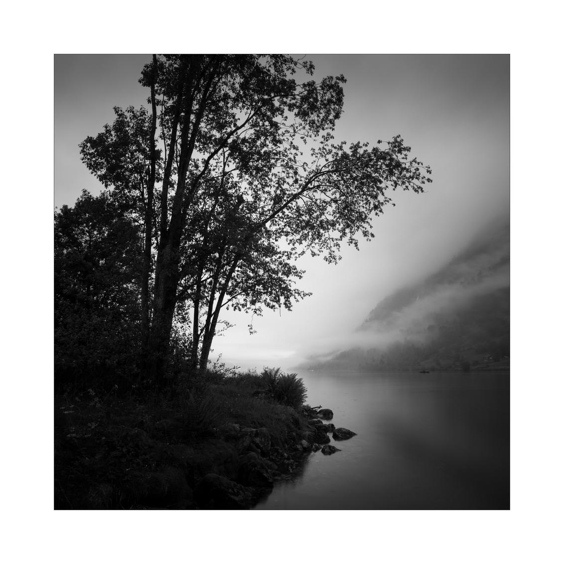 Northern Spirit. II - Oldedalen, Noorwegen. Foto gemaakt naast ons vakantiehuisje op een mistige ochtend.   Alweer een tijd geleden dat ik actief ben geweest op zoom, h - foto door Joshua181 op 24-12-2017 - deze foto bevat: wolken, water, natuur, vakantie, spiegeling, landschap, mist, bomen, bergen, meer, noorwegen, zwartwit, lange sluitertijd
