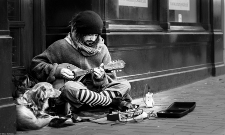 De straatmuzikant - Een straatmuzikant en zijn trouwe viervoeter. - foto door wilcofm op 30-05-2015 - deze foto bevat: man, mensen, portret, daglicht, jongen, zwartwit, straatfotografie, 50mm