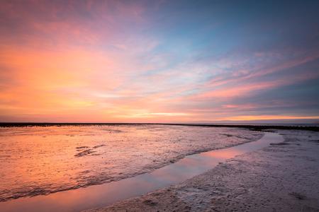 Wad Sahara - Sahara zand in de lucht, boven het wad - foto door ronaldrozema op 25-02-2021 - deze foto bevat: lucht, wolken, zon, zee, water, natuur, licht, winter, avond, zonsondergang, spiegeling, landschap, tegenlicht, zand, kust, friesland, wad, sahara, lange sluitertijd