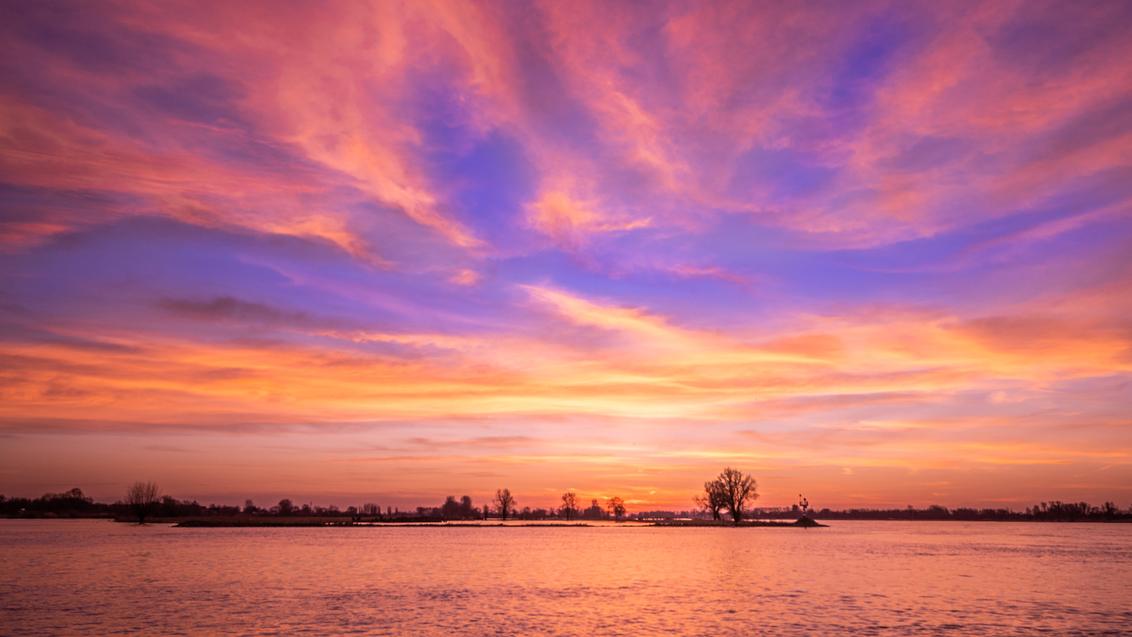 Explosie - Door alle berichten van het saharazand wat onze kant om komt, stond ik vanmorgen al ruim voor zonsopkomst bij de Merwerde. Of de lucht echt gekleurd  - foto door marielledevalk op 21-02-2021 - deze foto bevat: lucht, kleuren, wolken, paars, water, natuur, licht, oranje, winter, landschap, zonsopkomst, bomen, rivier, kleurrijk, polder, kleurenpracht, saharazand