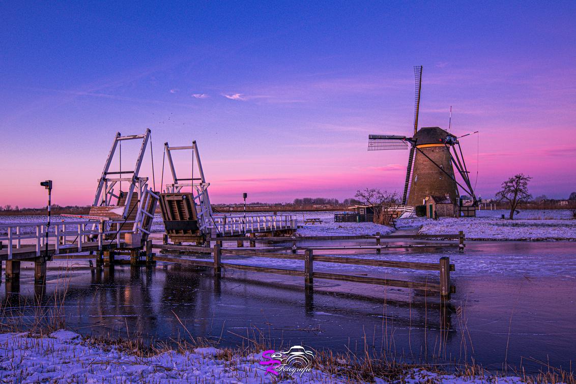 Kinderdijk - - - foto door samantharorijs op 25-02-2021 - deze foto bevat: lucht, wolken, zon, water, natuur, licht, sneeuw, winter, ijs, landschap, zonsopkomst, brug, molen, lange sluitertijd