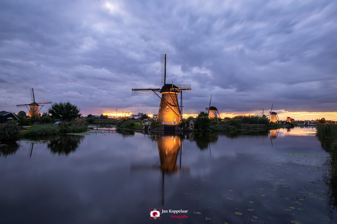 De rug toegekeerd - [b]De rug toegekeerd.[/b] Een foto van de verlichtingsweek 2020 in Kinderdijk (Zuid-Holland, Nederland). Helaas stonden de molens 'verkeerd'; met de - foto door fotografie-2 op 06-12-2020 - deze foto bevat: lucht, wolken, zon, water, dijk, natuur, licht, avond, zonsondergang, spiegeling, landschap, bomen, brug, molen, polder, kinderdijk, landschapsfotografie, zuid-holland, lange sluitertijd, jkoppelaar