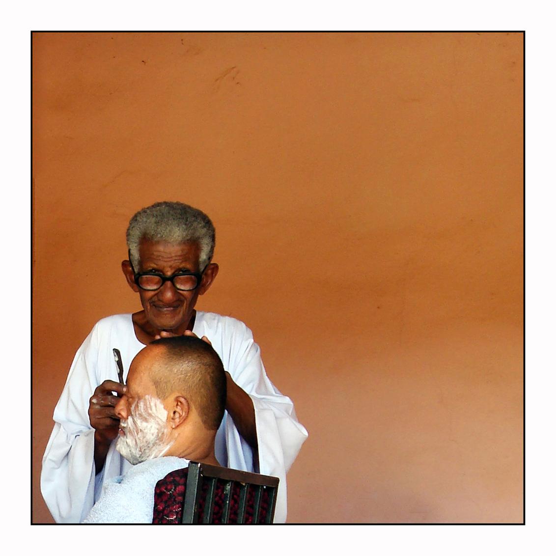 Do Not Disturb - In Omdurman, bij Khartoum liggen de fotomomenten voor het oprapen. Overal zeer vriendelijke mensen, zelfs als je ze stoort bij hun dagelijkse bezighe - foto door lokkjja op 19-07-2009 - deze foto bevat: rood, foto, oranje, vakantie, mooi, afrika, grijs, kapper, scheren, serieus, storen