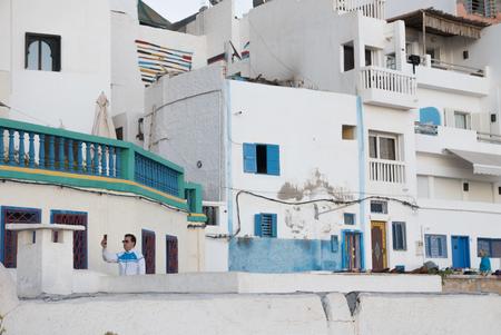 Taghazout - Face Time - Altijd verbonden zijn met de buiten-wereld, is tegenwoordig belangrijker geworden dan zelf kunnen genieten van je omgeving....  Genomen in Taghazou - foto door Krulkoos op 04-02-2020 - deze foto bevat: kleuren, kleur, straat, telefoon, blauw, reizen, mobiel, marokko, colour, straatfotografie, digitaal, pastel, verbonden, reisfotografie, pastels, colorful, morocco, pastelkleuren, maroc, Selfie, maurice weststrate, lx100, taghazout, typisch marokko, typical morocco, moroccan colors, colors of morocco, pastel colors, digitale tijdperk, facetime