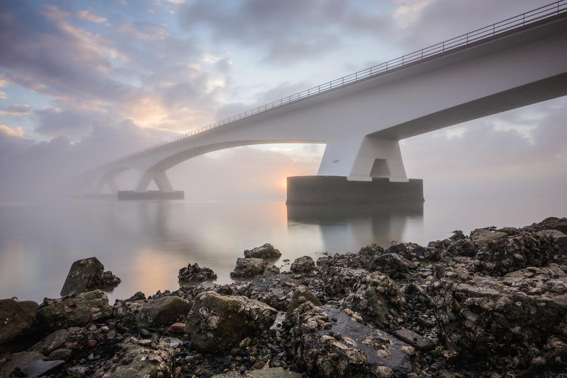 Zeelandbrug - De Zeelandbrug, de kenmerkende brug tussen Noord- Beverland en Schouwen-Duivenland is met 5022 meter de langste brug van Nederland! - foto door MaxterBurg op 01-09-2020 - deze foto bevat: lucht, wolken, zon, zee, water, licht, vakantie, architectuur, landschap, mist, tegenlicht, zonsopkomst, brug, zeeland, kust, kleurrijk, stenen, oosterschelde, zierikzee, rustgevend, sfeervol, voorgrond, zeelandbrug, pastelkleuren, colijnsplaat, lange sluitertijd, zeeuwse kust, grijsverloopfilters, oosterscheldebrug