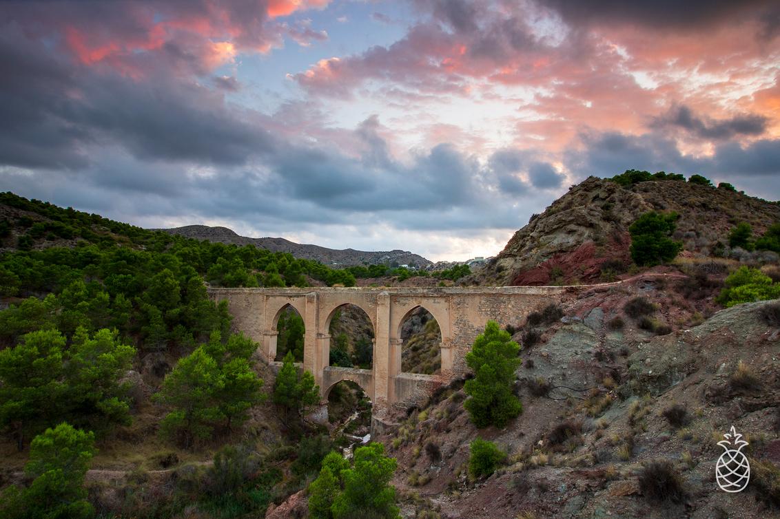Cuatro Ojos Four Eyes - De vier ogen zo word het aquaduct genoemd vanwege de vier bogen. Het is een oud, niet meer in gebruik zijnde aquaduct nabij Aspe in een prachtig nat - foto door HenkPijnappels op 06-08-2020 - deze foto bevat: lucht, wolken, zon, natuur, licht, avond, zonsondergang, landschap, bomen, bergen, brug, rivier, spanje, lange sluitertijd
