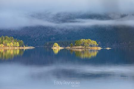 SHINE A LIGHT - Even kwam de zon tussen de laag hangende bewolking door en scheen prachtig over de kleine eilandjes in de Byglandsfjord (Noorwegen) - foto door eddy-reynecke op 16-03-2019 - deze foto bevat: lucht, wolken, zon, water, natuur, licht, herfst, vakantie, spiegeling, landschap, mist, bos, tegenlicht, bomen, bergen, meer, noorwegen, norway, lange sluitertijd, Byglandsfjord