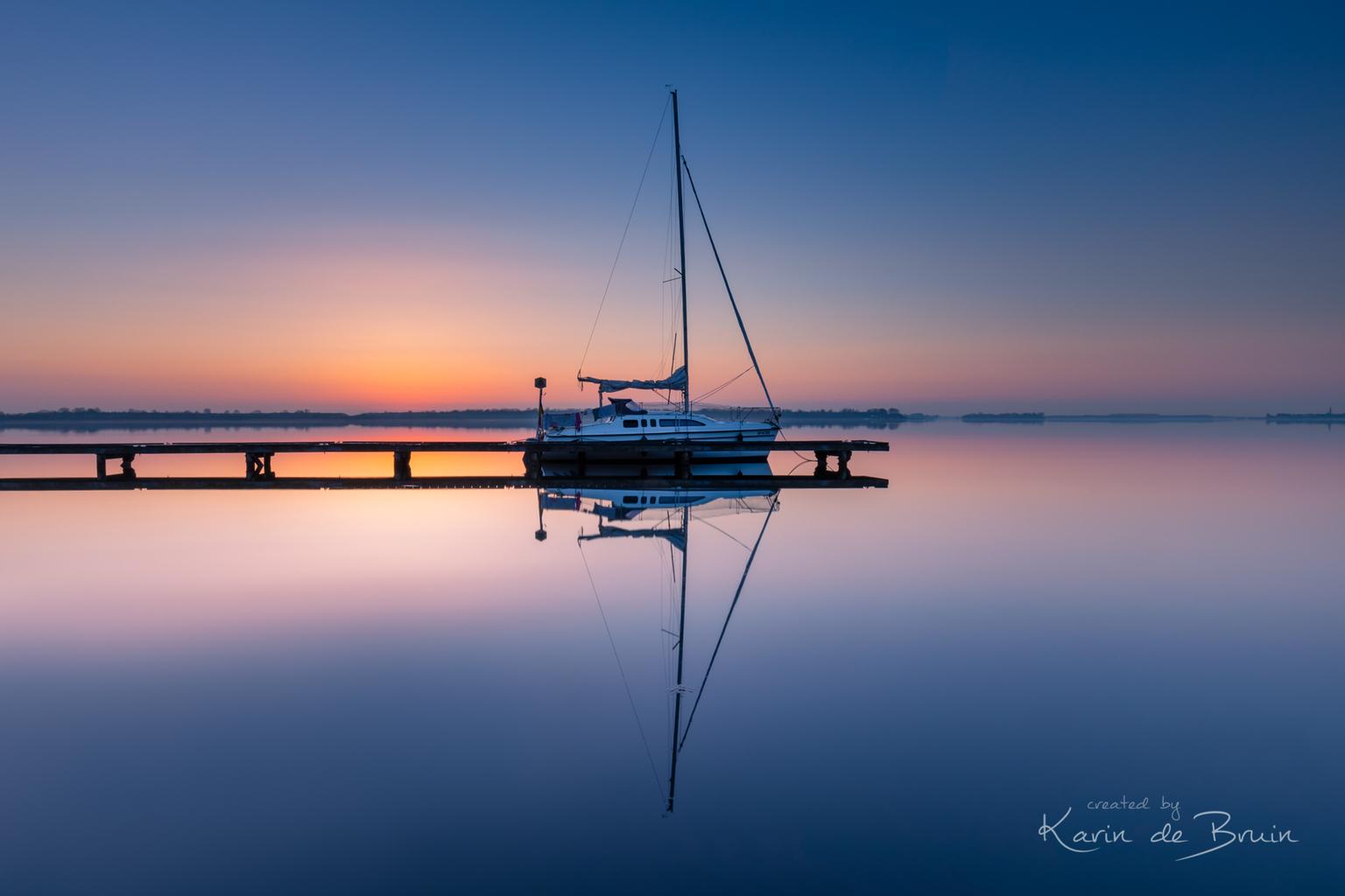 A quiet Morning! -   - foto door KarindeBruin op 13-04-2021 - locatie: Veerse Meer, 2134 VR Hoofddorp, Nederland - deze foto bevat: water, veerse meer, boot, zonsopkomst, steiger, zee;land, reflectie, spiegeling, water, lucht, watervoorraden, vloeistof, boot, vloeistof, waterscooters, schemer, meer, nagloeien