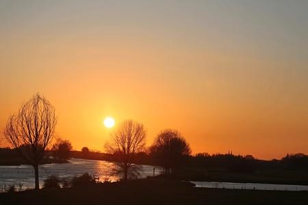 Zonsondergang boven de Maas - Vanaf het Genneperhuys - foto door Ebben op 13-04-2021 - deze foto bevat: lucht, water, atmosfeer, ecoregio, fabriek, natuurlijk landschap, nagloeien, boom, oranje, zonlicht
