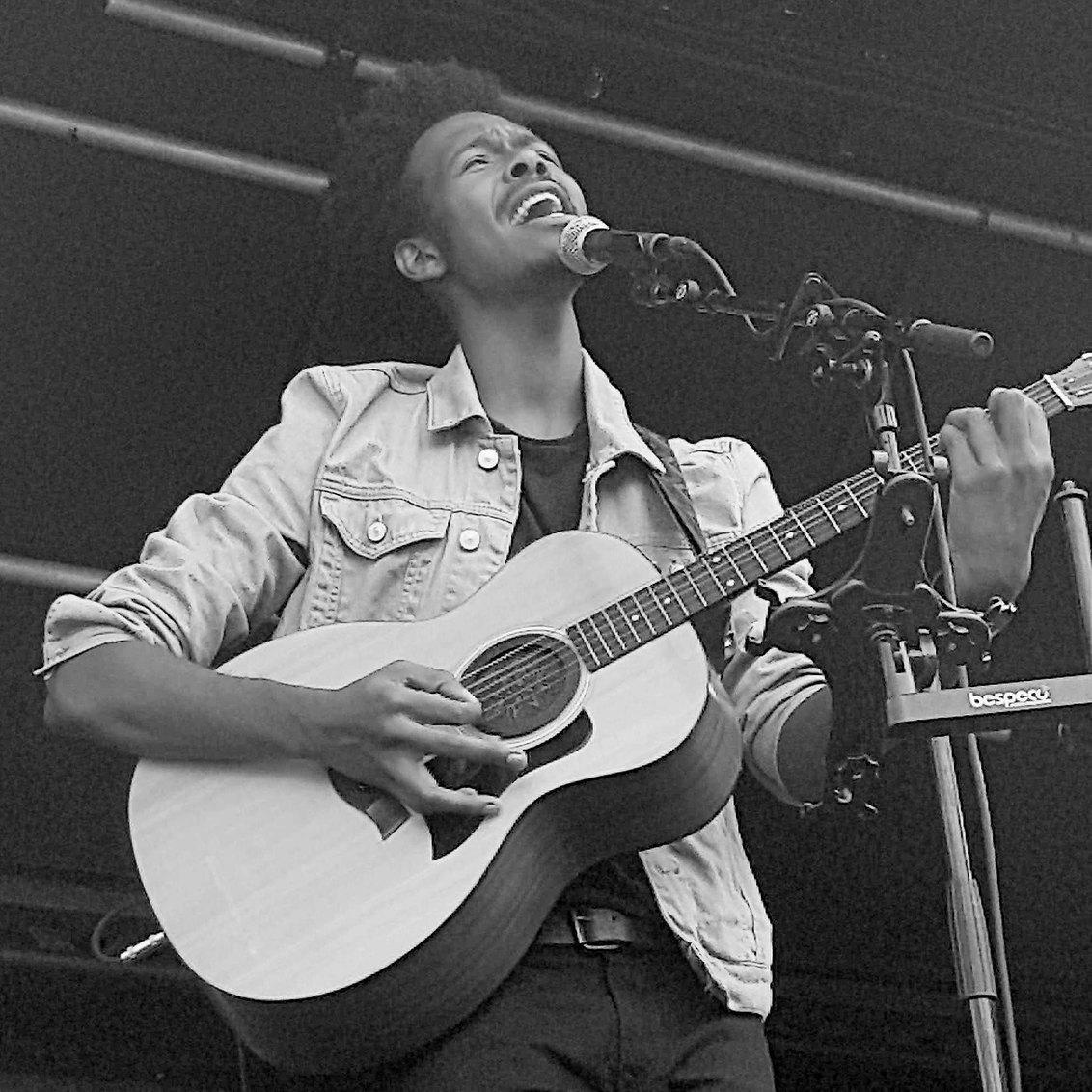 """Jeangu Macrooy - Jeangu Macrooy, sinds drie jaar woonachtig in Nederland, tijdens zijn optreden in Alkmaar vanmiddag in het kader van """"Zomer op het plein"""". Fantastisc - foto door Walvisch op 30-07-2017 - deze foto bevat: pop, artiest, gitaar, muziek, optreden, zingen, muzikant, geluid, kracht, alkmaar, soul, zwartwit, emotie, live, gitarist, zanger"""
