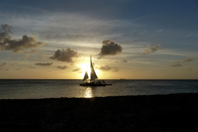 zonsondergang - tijd om aan te leggen - foto door Krea10 op 14-04-2021 - locatie: Aruba - deze foto bevat: wolk, lucht, water, boot, waterscooters, voertuig, nagloeien, mast, zeilboot, schemer
