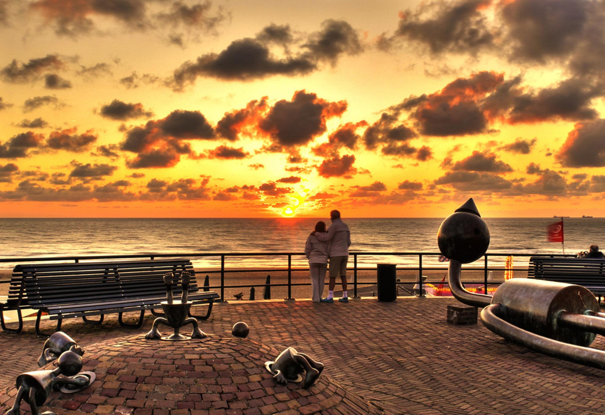 Sunset Scheveningen - Hdr opname van een zonsondergang in Scheveningen.  De mensen stonden redelijk stil waardoor de 5 opnames met statief nog redelijk gelukt zijn. De h - foto door MICHELD200 op 23-03-2010 - deze foto bevat: lucht, wolken, kleur, zon, strand, zee, zonsondergang, portret, beelden, hdr, romantisch, bewerkte fotografie - Deze foto mag gebruikt worden in een Zoom.nl publicatie