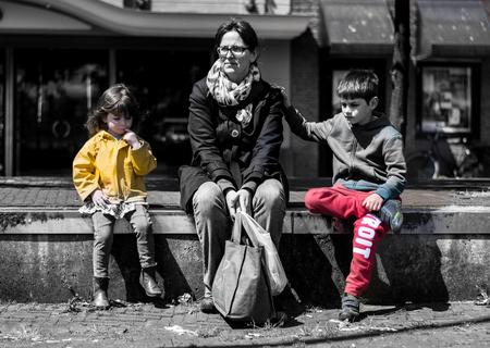 3 op een rij - Een moeder en haar twee kinderen rusten even uit tijdens een dagje uit in Leiden. - foto door wilcofm op 30-05-2015 - deze foto bevat: vrouw, mensen, portret, stad, zwartwit