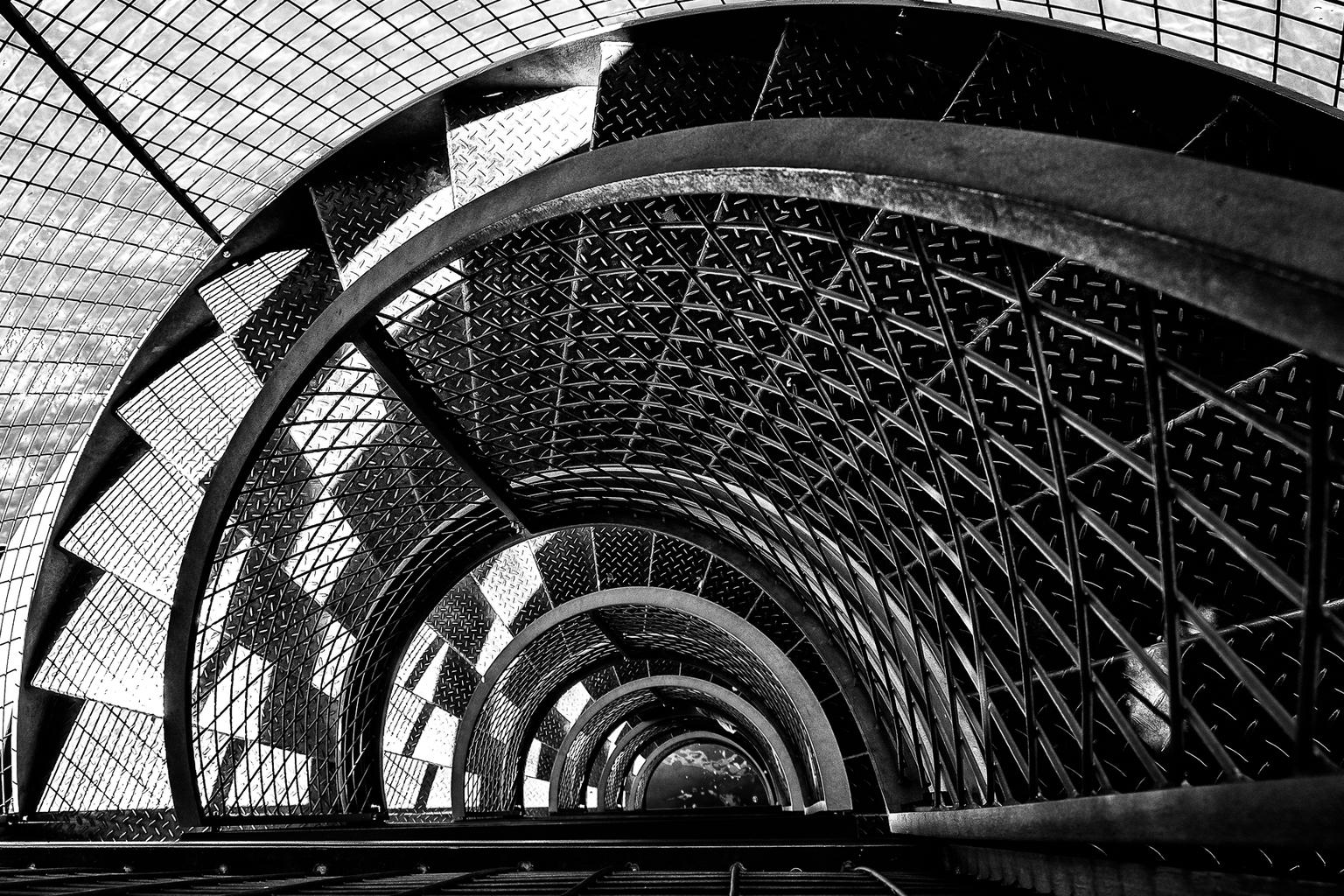 Wenteltrap - Wenteltrap die mij opviel door met name het licht dat met de trap speelde. - foto door josdidden op 05-05-2021 - locatie: Friedrichshafen, Duitsland - deze foto bevat: zwart-wit, zwartwit, trap, schaduw, wenteltrap, grafisch, wit, zwart, architectuur, zwart en wit, autoband, stijl, lijn, automotive wielensysteem, tinten en schakeringen, cirkel