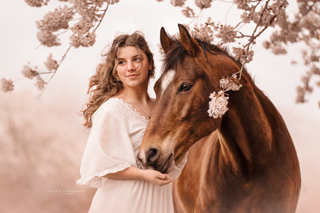 Meisje en paard onder een bloesemboom - Meisje en paard onder een bloesemboom op lentedag met veel wind. - foto door HiltsjeFotografie op 11-04-2021 - deze foto bevat: bloesem, paard, portret, lente, paard, hoofd, oog, glimlach, boom, werkend dier, flitsfotografie, lever, gelukkig, wimper