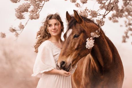 Meisje en paard onder een bloesemboom