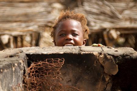 Little girl smile - Cute little girl smiling and peeking out above a dirty concrete wall in Senegal - foto door TTOnline op 07-08-2018 - deze foto bevat: mensen, bruin, klein, oranje, vakantie, portret, reizen, ogen, haar, tanden, lachen, meisje, lief, glimlach, muur, afrika, hoofd, jong, kijken, cultuur, straatfotografie, gelukkig, beton, toerisme, gluren, vies, blij, afro, reisfotografie, schattig, kroeshaar, arfikaans, senagal