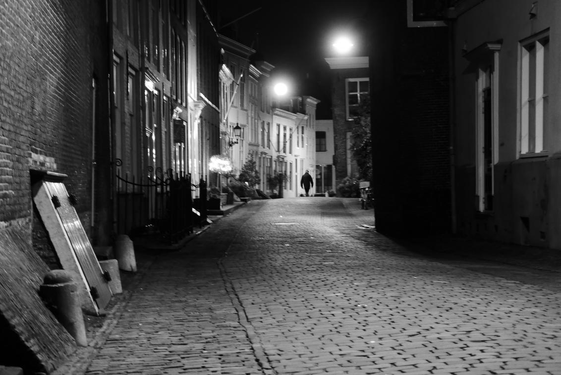 Middelburg - Alleen in de straat - Avondsfeer in Middelburg, Zeeland. - foto door Krulkoos op 03-03-2020 - deze foto bevat: oud, straat, avond, silhouette, eenzaam, stad, zeeland, nacht, binnenstad, zwartwit, nachtfotografie, wandelen, straatfotografie, middelburg, straatje, alleen, wandelaar, avondfotografie, klinkers, leica, maurice weststrate, lx100, molstraat