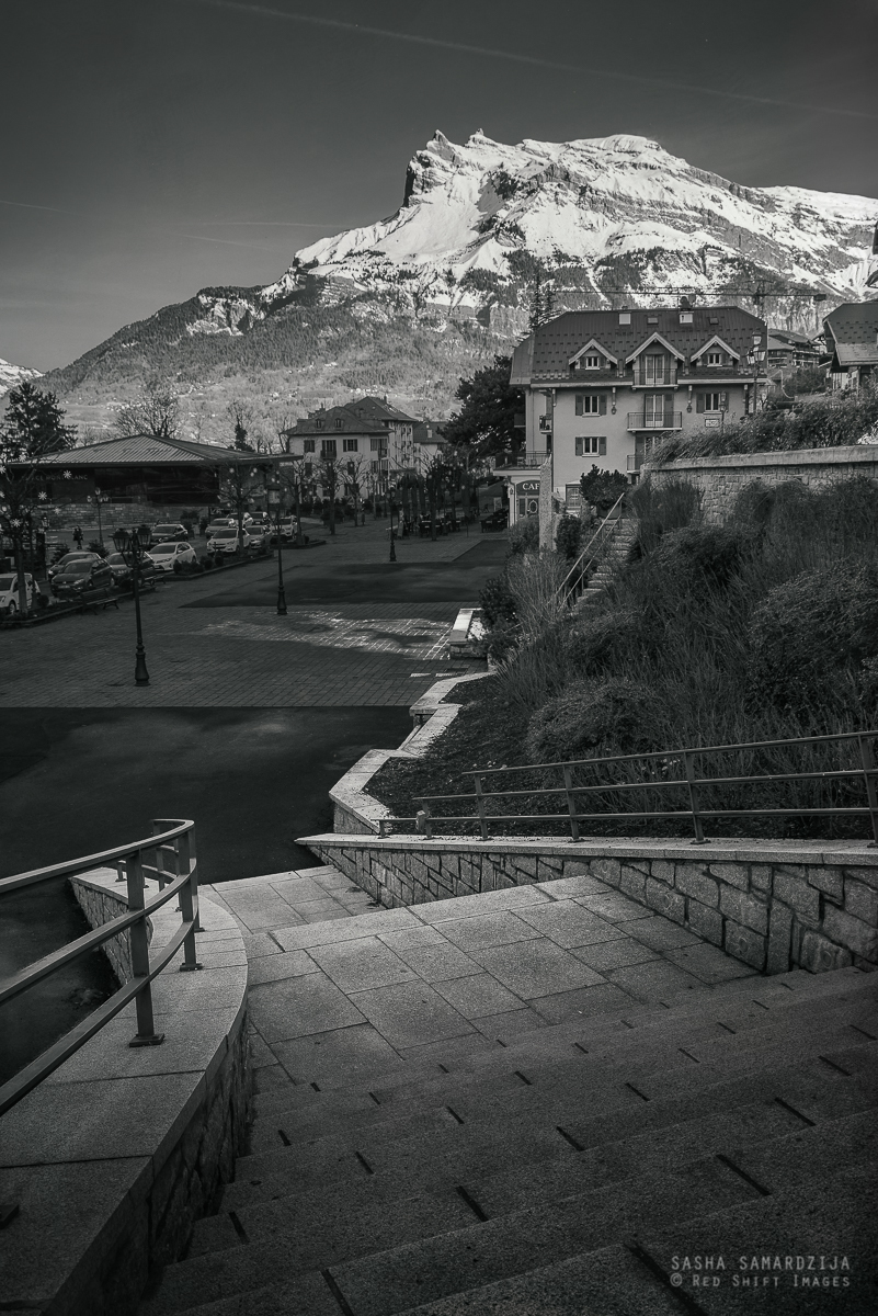Stairways to mountain - Village street and stairs and a big mountain in distance on French Alps, Saint Gervais Les Bains, France - foto door samards op 01-11-2017 - deze foto bevat: house, sport, high, street, home, travel, landscape, valley, city, white, top, france, sky, snow, hills, stairs, building, stone, beautiful, village, sunny, peak, outdoor, alps, mountain, fence, traditional, adventure, summit, aerial, tourism, alpine, ascending, stairways, Sightseeing, Mountaineering, steep, leading lines, altitude, visit