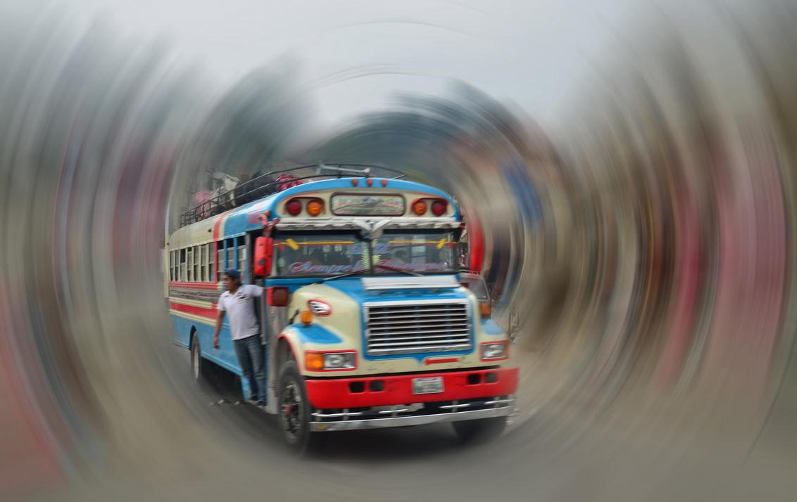 Bus van allertijden. - De afgedankte schoolbus uit de USA, wordt in Guatemala opgepimpt en is daar nagenoeg altijd in beweging. Naast de chauffeur hangt er een bijrijder in - foto door Floriscal op 05-09-2012 - deze foto bevat: guatemala, draaikolk, Radial blur, amerikaanse schoolbus