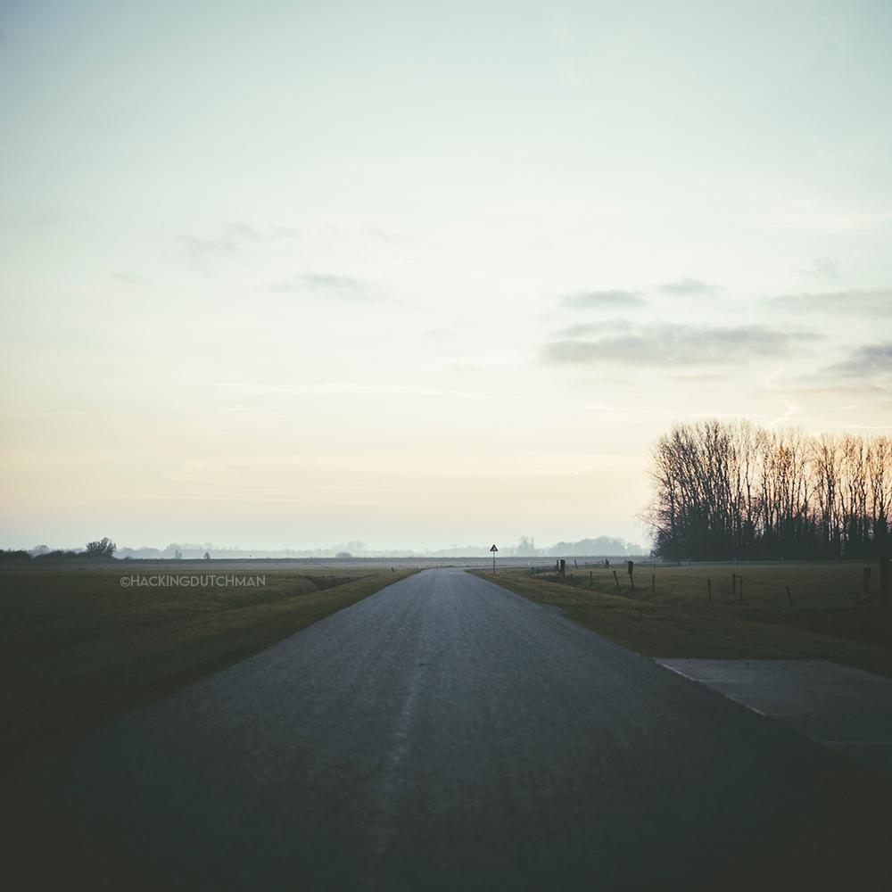 Weg - Een weg die naar rechts buigt.     ©MotionMan 2021 - foto door motionman op 03-03-2021 - deze foto bevat: lucht, kleuren, wolken, kleur, zon, uitzicht, natuur, avond, zonsondergang, landschap, mist, bomen, perspectief, lange, sfeer, verkeersbord, dauw, weg, friesland, horizon, bord, ondergang, scherpe, pastel, bocht, sfeervol, lang, scene, katlijk, scenisch, scherpebocht