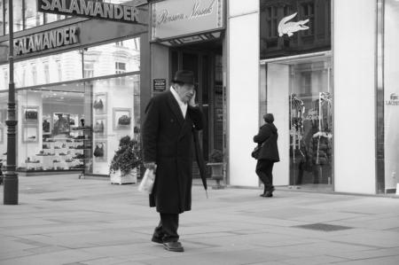 """Mobiele communicatie - Deze man liep volledig opgaand in zijn telefoongesprek door de """"kalverstraat"""" van Wenen. De luxe winkels met  merk kleding ontgingen aan zijn aandach - foto door frenchfries op 28-02-2012 - deze foto bevat: man, bellen, gsm, wandelen, straatfotografie, lopen, wenen, winkelstraat"""
