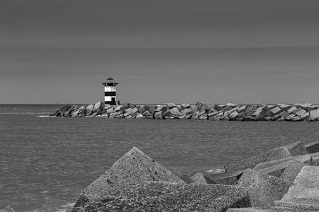 baken in de nacht - vuurtoren Scheveningen - foto door carbone op 13-04-2021 - locatie: Scheveningen, Den Haag, Nederland - deze foto bevat: vuurtoren, lucht, water, zwart, toren, lichaam van water, zwart en wit, grijs, kust- en oceanische landvormen, horizon