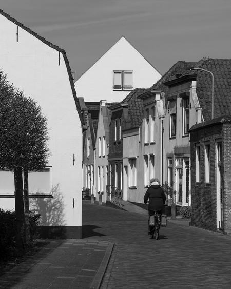 Rust - Fietser in Dirksland - foto door capture1 op 10-04-2021 - deze foto bevat: fiets, gebouw, fabriek, wiel, fotograaf, venster, lucht, band, infrastructuur, zwart