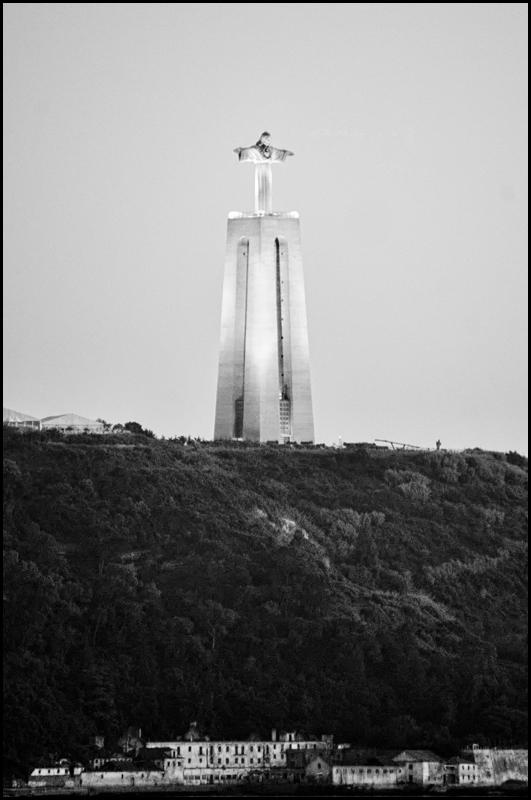 Lisboa 02 - Geloof is een van de belangrijkste dingen in Portugal. En dat kun je dan ook overal zien. Zo ook aan de revier de Taag. Daar staat een gigantisch Chr - foto door mphvanhoof_zoom op 08-08-2017 - deze foto bevat: beeld, reizen, jezus, portugal, lissabon, toerisme, reisfotografie, stedentrip, zwart wit, Cristo Rei