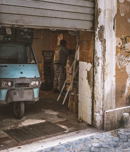 Roma - Een man bezig in zijn werkplaats in Rome, - foto door MHVDE op 23-05-2018 - deze foto bevat: oud, rome, monkey, werkplaats, car, garage, mhvde, vespa car