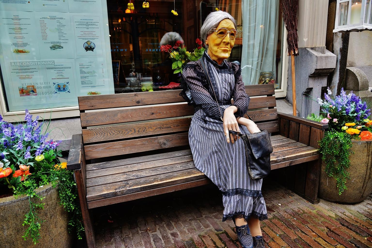 Welkom Corona Vrij..... - .... Deze vriendelijke oudere dame , wacht met heel veel ongeduld op betere tijden! Beste Zoomers en kijkers het beste moet nog komen! Groetjes, Fran - foto door f.arts1 op 12-04-2021 - locatie: Groenmarkt, 3311 BE Dordrecht, Nederland - deze foto bevat: fabriek, bloempot, bloem, purper, heeft, kamerplant, geel, straatmode, hout, zonnehoed