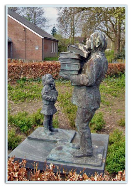 Man en meisje bij de bibliotheek. - Foto genomen in Zuiwolde (Dr.). De man neemt een stapel (studie)boeken mee naar huis, het meisje staat er verbaasd naar te kijken. De vogels denken e - foto door heljo op 10-03-2010