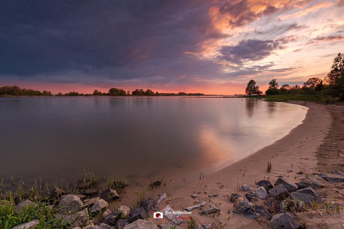 The power of beautiful nature - [b]The power of beautiful nature.[/b] Een foto uit de oude doos, opnieuw bewerkt. Deze foto is gemaakt aan rivier De Waal, nabij vuren (Gelderland,  - foto door fotografie-2 op 21-03-2021 - deze foto bevat: lucht, wolken, zon, strand, water, dijk, lente, natuur, licht, avond, zonsondergang, spiegeling, landschap, tegenlicht, bomen, rivier, hdr, landschapsfotografie, lange sluitertijd, jkoppelaar