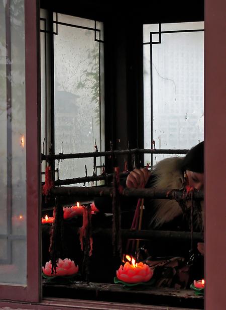 Offer moment - Nanjing: In de Buddistische Jiming temple (letterlijk betkent het 'Kraaiende Haan') wordt het geloof nog actief beleefd door jong en oud. De tempel i - foto door shona op 29-09-2011 - deze foto bevat: roze, vrouw, portret, china, tempel, kaars, gebed, intiem, geloof, ritueel, nanjing