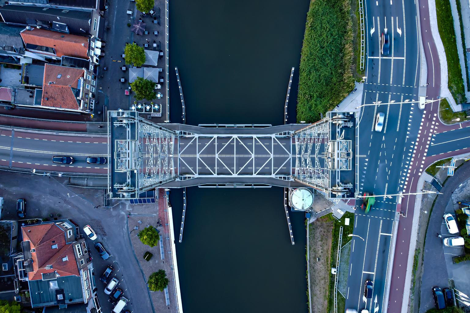 Hefbrug Waddinxveen - De Waddinxveense hefbrug over dr Gouwe van boven. Dit monument is een geliefd maar ook een gehaat object. Dit omdat als er een schip onder de brug do - foto door EusDriessen op 12-04-2021 - locatie: Kerkweg-Oost 329-381, 2741 HE Waddinxveen, Nederland - deze foto bevat: drone, waddinxveen, hefbrug, gouwe, rivier, hoogte, water, infrastructuur, fabriek, stedelijk ontwerp, gebouw, lijn, landschap, doorgaande weg, oriëntatiepunt, weg