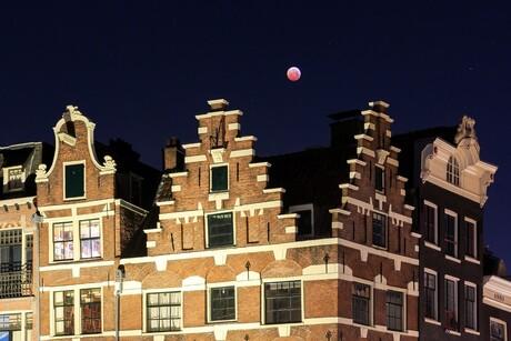 Maansverduistering boven de grachtenpanden in Amsterdam