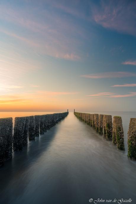Golfbreker op het strand van Domburg tijdens de zonsondergang