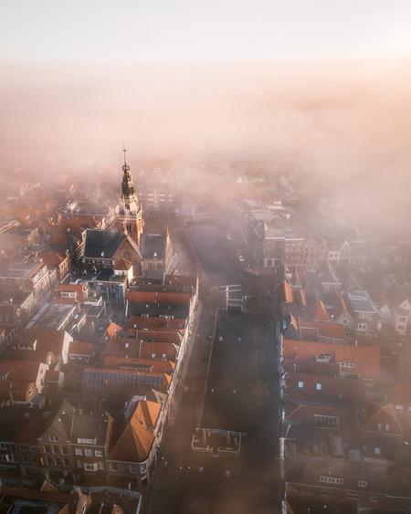 Mistig Alkmaar. - Een mistige ochtend in mijn mooie stad, Alkmaar. Op de foto is de Waagtoren mooi uitgelicht waardoor deze meteen de aandacht trekt. - foto door Larissavhooren op 05-03-2021 - deze foto bevat: kleur, straat, licht, architectuur, mist, kerk, stad, alkmaar, gracht, straatfotografie, centrum, fog, zoomnl, geboorteplaats, Noord Holland, binnestad, drone, dronefoto