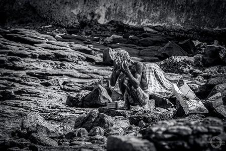 Bath of the poor. - Een man die zich wast op het grillige rotsstrand van Mumbai in India. - foto door eyefocus-76 op 09-04-2013 - deze foto bevat: man, arm, india, rotsen, armoede, wassen, zittend, mumbai, zwart wit, hurkend, bade