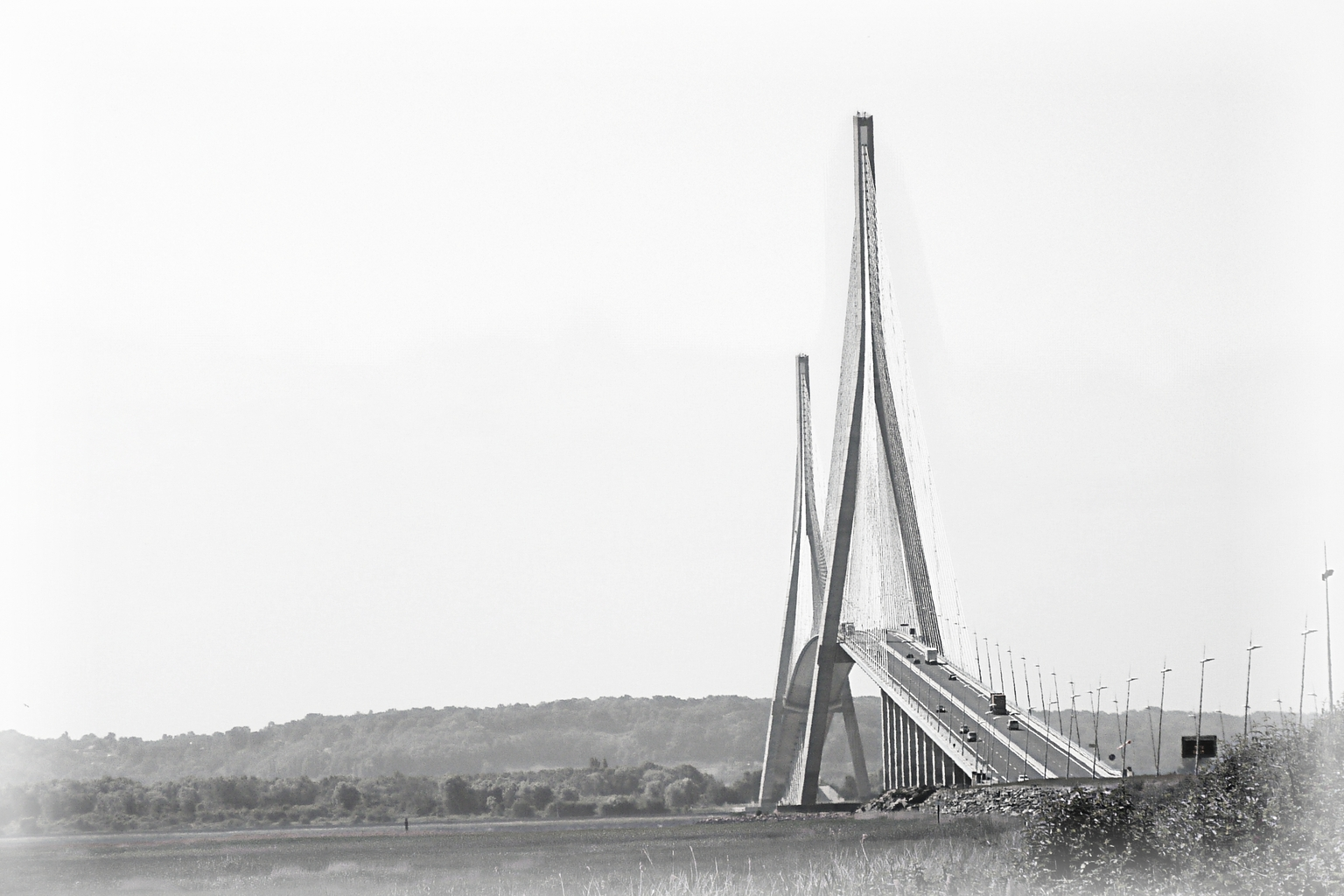 Pont de Normandie - - - foto door onne1954 op 22-04-2021 - deze foto bevat: brug, pont de normandie, frankrijk, zwartwit, lucht, voertuig, water, horizon, balkbrug, landschap, weg, brug, tuibrug, betonnen brug