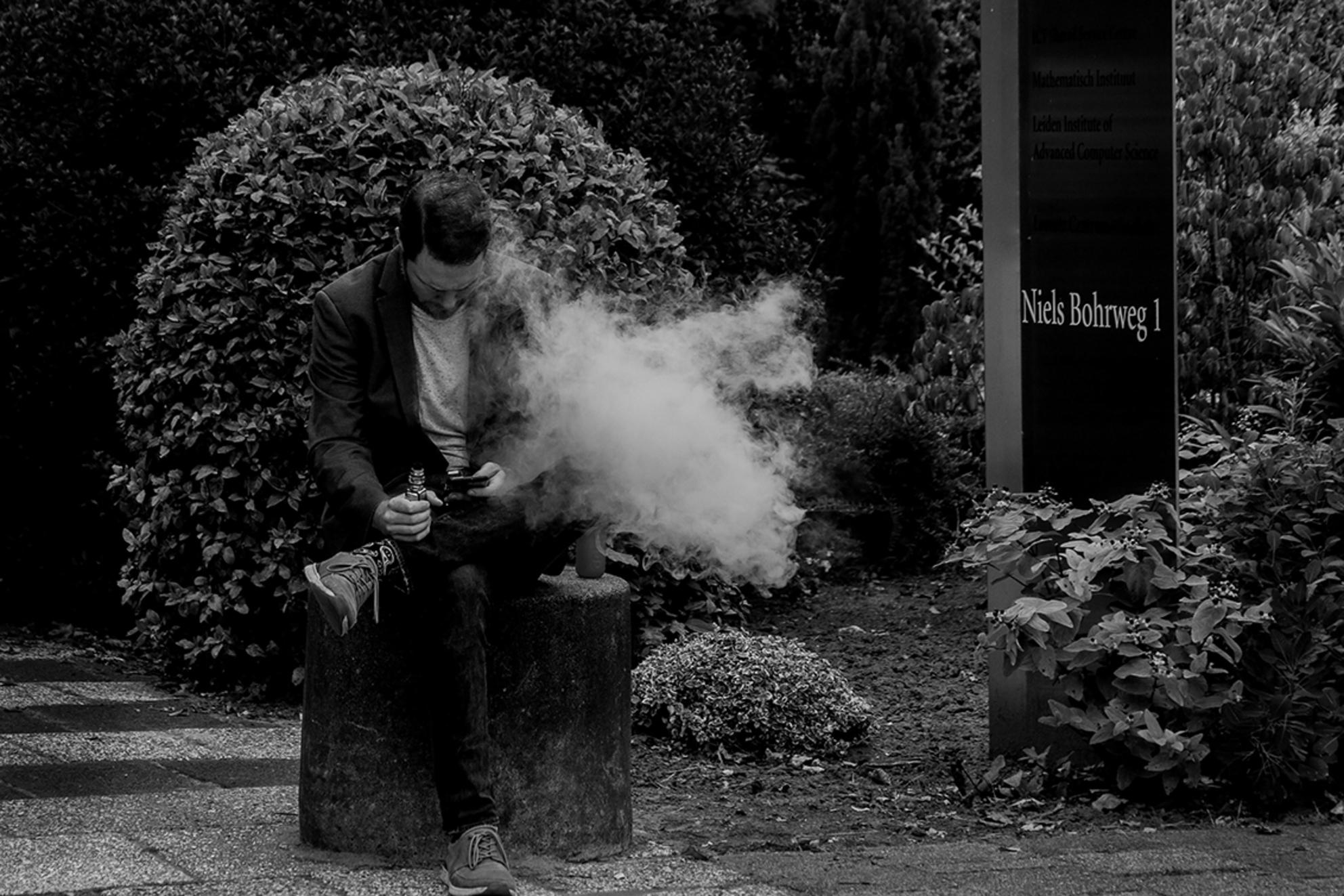 E-dampen - In je pauze lekker E-dampen - foto door nak-kos op 04-05-2020 - deze foto bevat: man, leiden, zwartwit, roken, straatfotografie, sigaret - Deze foto mag gebruikt worden in een Zoom.nl publicatie