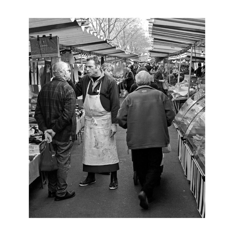 straat 9 - ......markt in Parijs..... de slager stapte even uit zijn kraam en besprak de politieke situatie in het land.... ...en dat allemaal in het Frans... - foto door bernhard48 op 06-02-2018 - deze foto bevat: mensen, straat, markt, parijs, zwartwit, straatfotografie