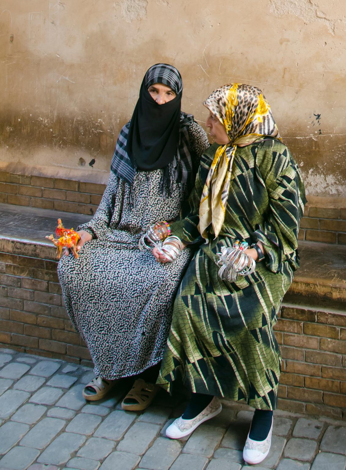 Verkoopsters in Marrakesh - Twee vrouwen die aan het wachten waren op klanten die het museum uitkwam in Marrakesh - foto door Felice_zoom op 14-11-2015 - deze foto bevat: vrouw, mensen, vakantie, portret, reizen, stad, marokko, cultuur, straatfotografie, kameel, geloof, toerisme, gesluierd, dromedaris, reisfotografie, marrakesh, armbanden