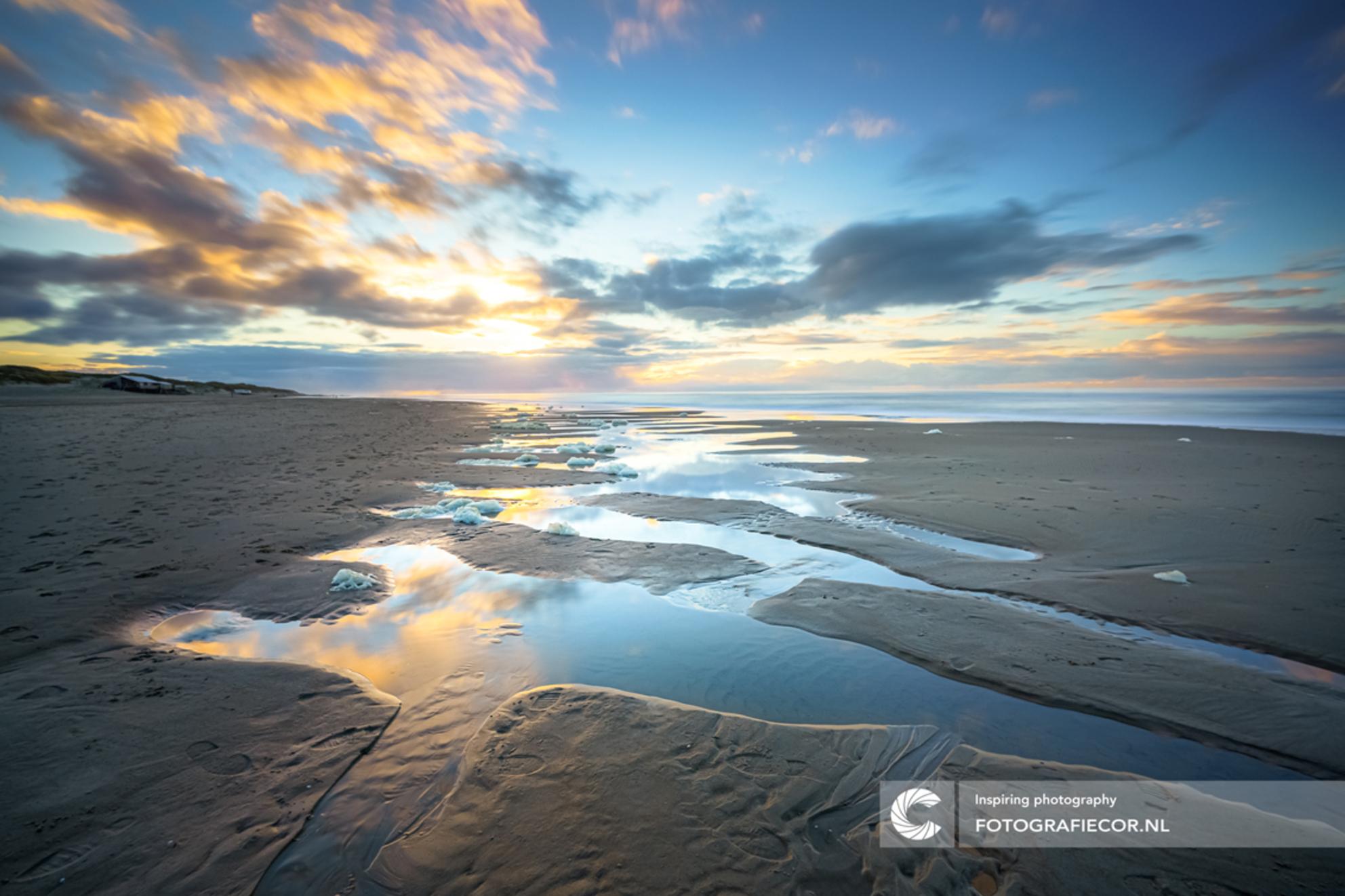 Ritmiek en dynamiek aan het strand - Een magisch momentje op de Noordzee stranden van het Waddeneiland Texel. De dynamiek van de lucht en patronen op het strand lijken samen te komen en  - foto door Fotografiecor op 26-02-2021 - deze foto bevat: lucht, wolken, zon, strand, zee, water, natuur, licht, avond, zonsondergang, vakantie, spiegeling, landschap, duinen, tegenlicht, zonsopkomst, zand, kust, lange sluitertijd - Deze foto mag gebruikt worden in een Zoom.nl publicatie