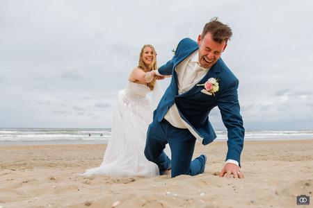 De bruidegom wil er vandoor - De bruidegom wil er vandoor op het strand van Zandvoort.  - foto door robinlooy op 12-04-2021 - locatie: Zandvoort, Nederland - deze foto bevat: trouwen, bruid, bruidegom, bruidspaar, komisch, grappig, strand, zandvoort, photoshoot, fotoshoot, trouwfotograaf, trouwfotografie, water, glimlach, lucht, trouwjurk, bruid, wolk, mensen op het strand, mensen in de natuur, bruidskleding, azuur