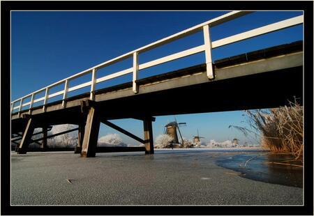 Onder de brug door ... - Dacht eens een ander standpunt te nemen en ben plat op het ijs gaan liggen. Vind het zelf wel apart de brug op deze manier in beeld, omdat je dit zo - foto door Foto_Marleen op 18-01-2009 - deze foto bevat: lucht, ijs, brug, molens, kinderdijk