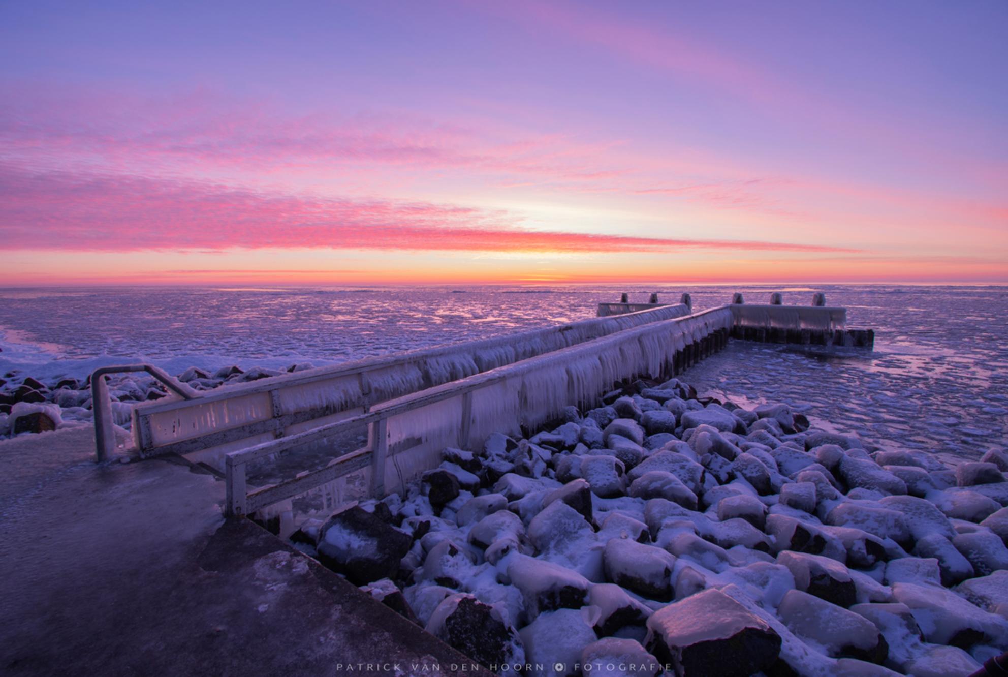 Amazing sunrise - Wat was het prachtig vanochtend! Qua kleur is deze foto onbewerkt, zo mooi was het. De lucht was zo paars dat zelfs de besneeuwde stenen paars kleu - foto door Patrick-van-den-Hoorn op 14-02-2021 - deze foto bevat: roze, lucht, wolken, paars, zon, water, sneeuw, ijs, tegenlicht, zonsopkomst, monument, steiger, ijspegels, afsluitdijk, onbewerkt, ijsklomp - Deze foto mag gebruikt worden in een Zoom.nl publicatie