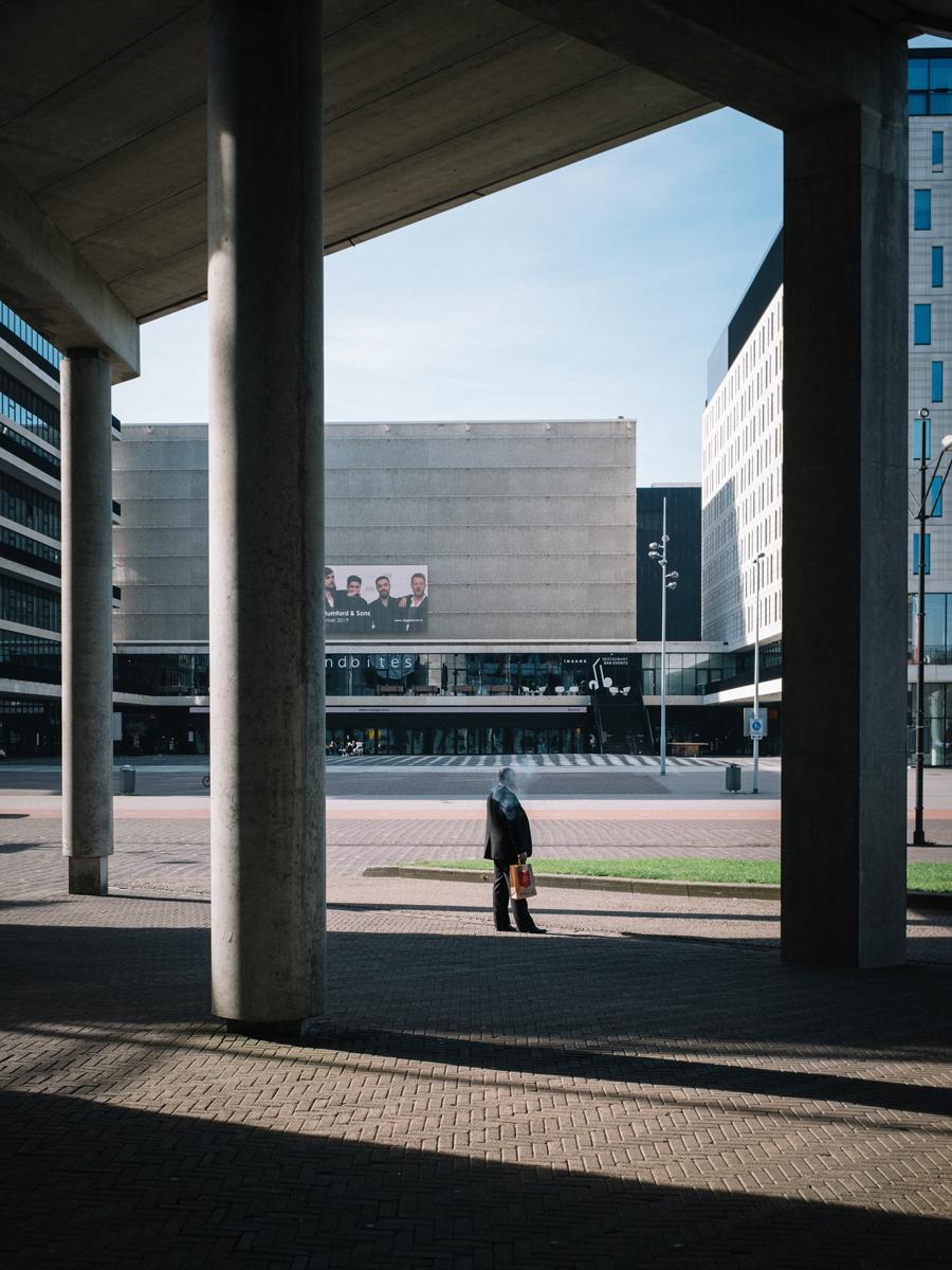 Man On Fire - Straatfotografie Amsterdam - foto door Northstar76 op 15-04-2021 - deze foto bevat: gebouw, lucht, schaduw, weg oppervlak, stad, weg, tinten en schakeringen, asfalt, trottoir, symmetrie